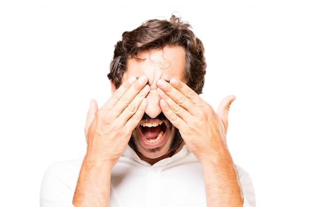 Człowiek zasłaniając oczy rękami
