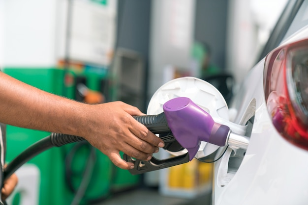 Człowiek zatankować samochód na stacji benzynowej do podróży