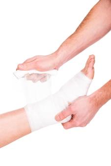 Człowiek zbliżenie kładzie bandaż na rannych stopach.