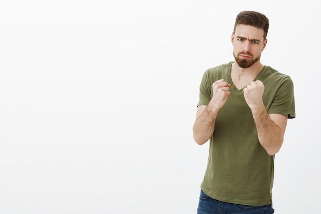 Człowiek zdecydowany walczyć z kaloriami po wakacjach. portret przystojny, poważnie wyglądający, wściekły brodaty facet w koszulce marszczy brwi, robi przerażającą minę, gdy trzyma pięści jak bokser, chcąc uderzyć i pokonać osobę