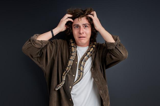 Człowiek zdezorientowany nie wie, co zrobić z wężem na sobie, złapał się za głowę, wstał w szoku