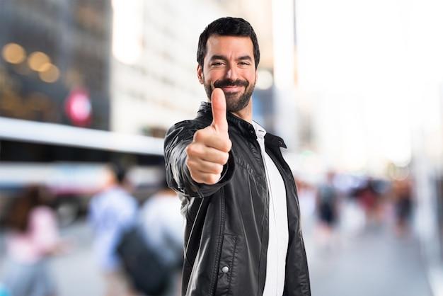 Człowiek ze skórzaną kurtką z kciukiem do góry