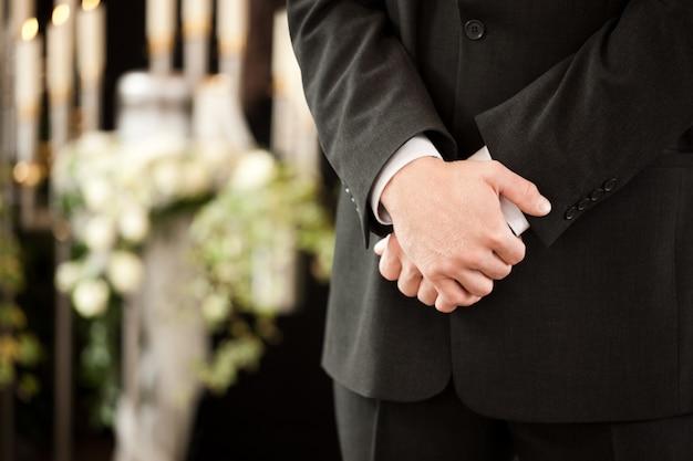 Człowiek ze skrzyżowanymi rękami na pogrzebie