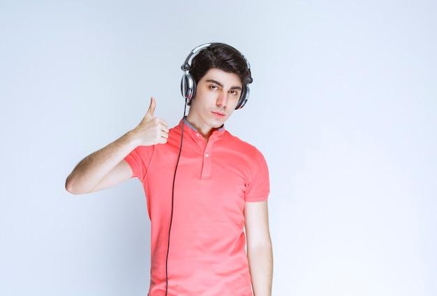 Człowiek ze słuchawkami pokazując kciuk do góry.