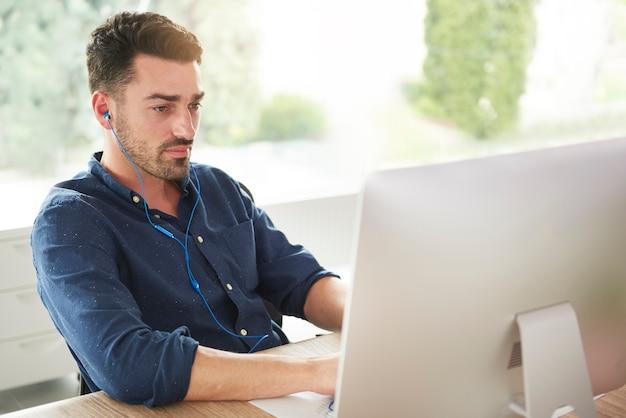 Człowiek ze słuchawkami pracuje na komputerze