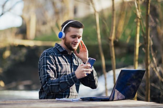 Człowiek ze słuchawkami pracuje na laptopie i używa smartfona