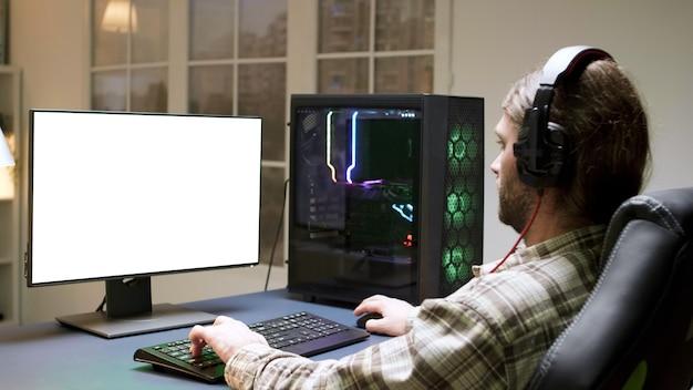 Człowiek ze słuchawkami siedzi na fotelu do gier, grając w gry na komputerze z zielonym ekranem.