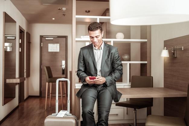 Człowiek ze smartfonem. młody biznesmen ciemnowłosy czyta jego listy biznesowe na czerwonym smartfonie