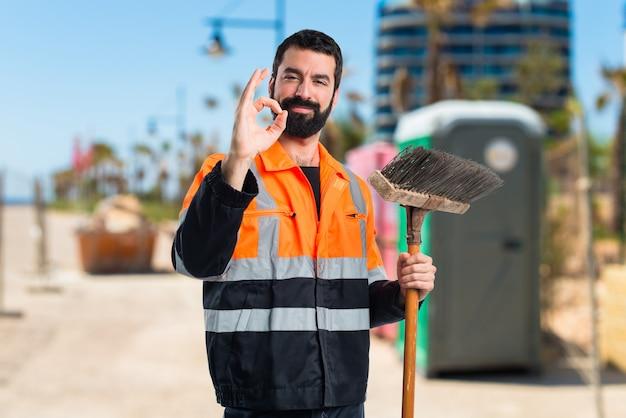 Człowiek ze śmieciami czyniąc znak ok