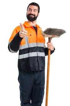 Człowiek ze śmietnikiem z kciukiem do góry