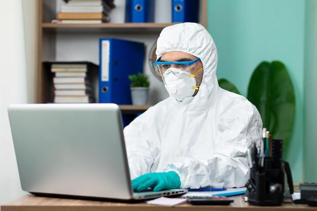 Człowiek ze specjalnym białym pakietem pracującym na laptopie w biurze