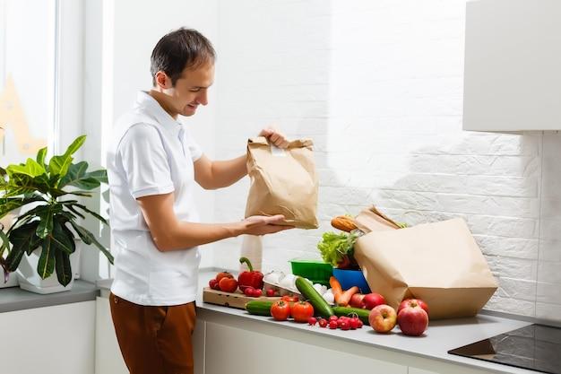 Człowiek ze świeżymi produktami przy stole w pomieszczeniu, zbliżenie. dostawa jedzenia
