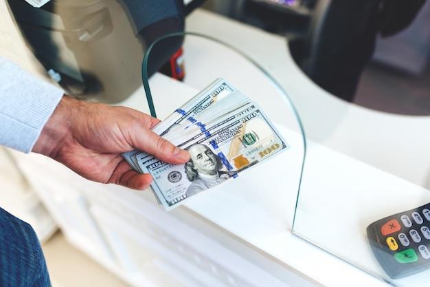 Człowiek zmienia pieniądze w kantorze, duża suma dolarów, wzrost kursu walutowego, zbliżenie pieniędzy zmieniających ręce ludzi