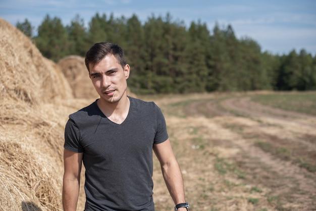 Czołowy autentyczny portret młodego mężczyzny w szarej koszulce na tle pola ze stogami siana