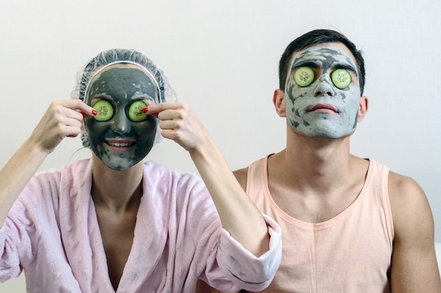 Czołowy portret małżeństwa z glinianymi maskami na twarzy i ogórkami przed nim. spa w domu. ochrona skóry