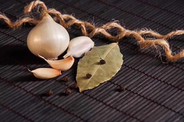 Czosnek, cebula, liść laurowy, czarny pieprz na czarnym stole.