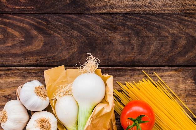 Czosnek i cebula w pobliżu pomidorów i spaghetti
