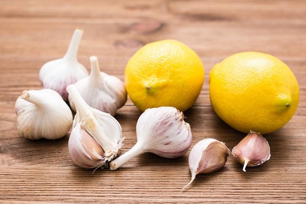 Czosnek i cytryna na drewnianym stole. medycyna alternatywna, leczenie środkami ludowymi. obniż poziom cholesterolu