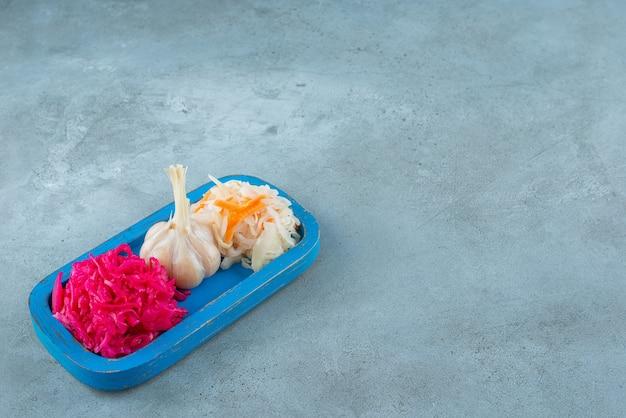 Czosnek i kapusta kiszona na drewnianym talerzu, na marmurowym stole.