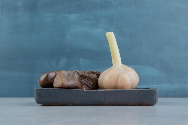 Czosnek i ogórki bakłażana na drewnianym talerzu na marmurowej powierzchni