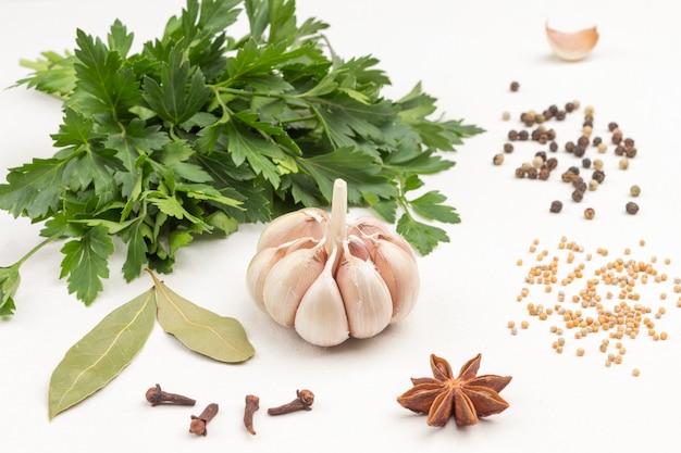 Czosnek i przyprawy na białej powierzchni. zdrowe odżywianie na przeziębienia. terapia alternatywna