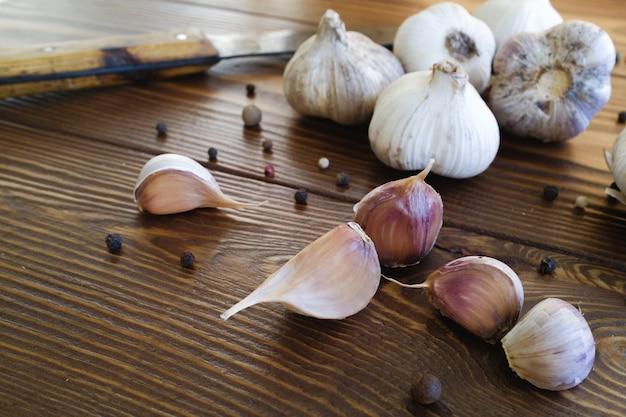 Czosnek i przyprawy na drewnianym stole.