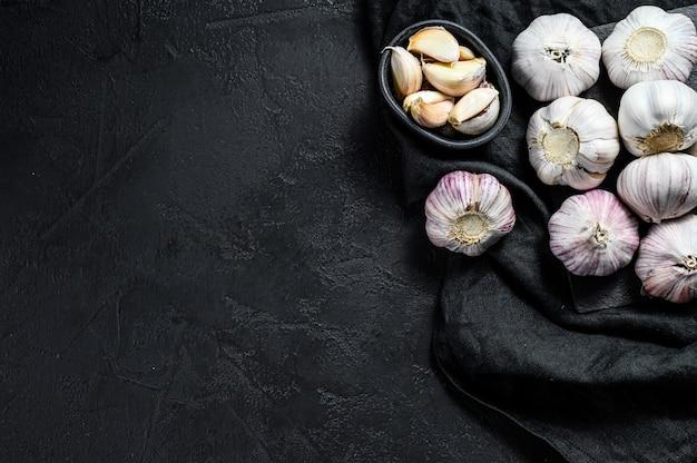 Czosnek i ząbki czosnku na desce do krojenia. ekologiczna żywność rolnicza. czarne tło. widok z góry