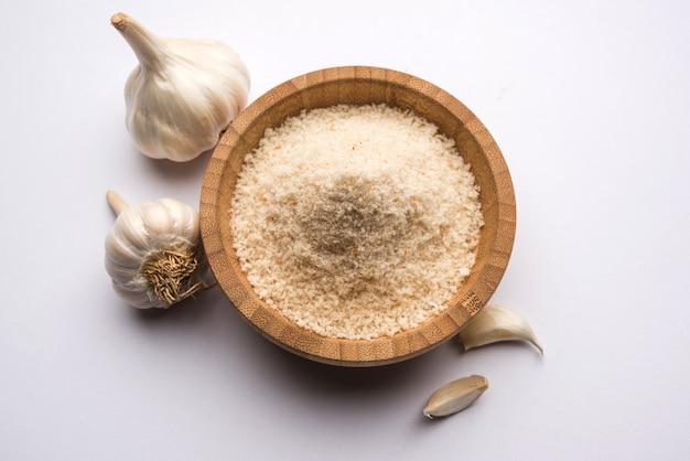 Czosnek lub proszek lahsun to mielony, odwodniony czosnek. to powszechna przyprawa do makaronów, pizzy i grillowanego kurczaka. na białym tle, selektywne skupienie