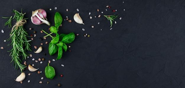 Czosnek, olej i przyprawy na czarnym tle. wysokiej jakości zdjęcie