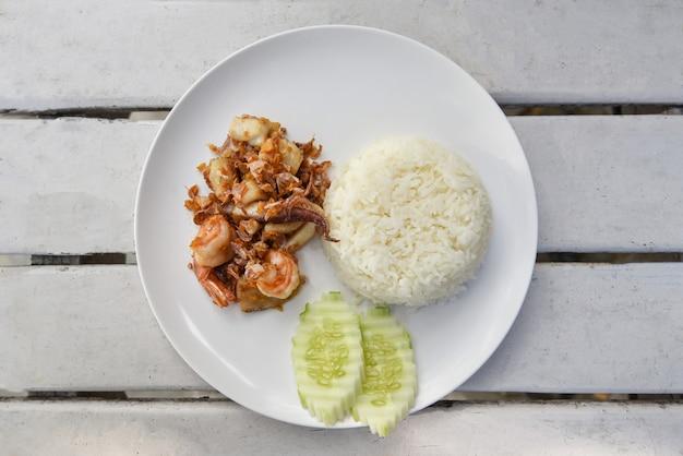 Czosnek smażone owoce morza / smażone krewetki kalmary z ryżem na białym talerzu i ogórkiem