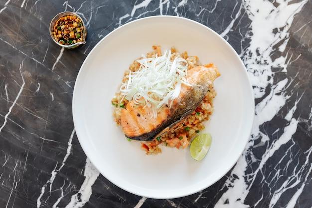 Czosnek smażony ryż z grillowanym łososiem serwowany z sosem z fasoli chili na czarnym marmurowym stole.