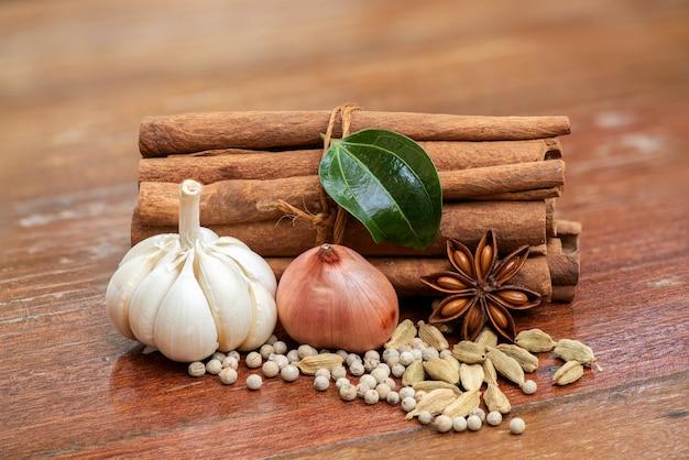 Czosnek, szalotka, cynamon, zielony liść cynamonu, papryka, zielony kardamon i anyż na starym drewnie.