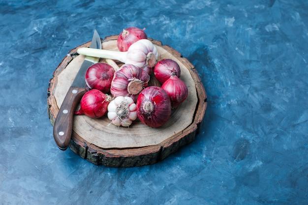Czosnek z czerwoną cebulą, nóż na nieczysty niebieskiej i drewnianej desce, wysoki kąt widzenia.