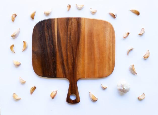 Czosnek z drewnianą deską do krojenia na bielu