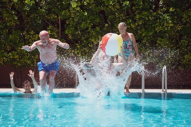 Czterech beztroskich ludzi bawiących się w odkrytym basenie skaczących z pluskającą wodą koncepcja lato i wakacje