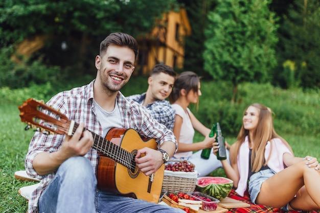 Czterech młodych atrakcyjnych osób w parku, a jeden z nich gra na gitarze i uśmiecha się.