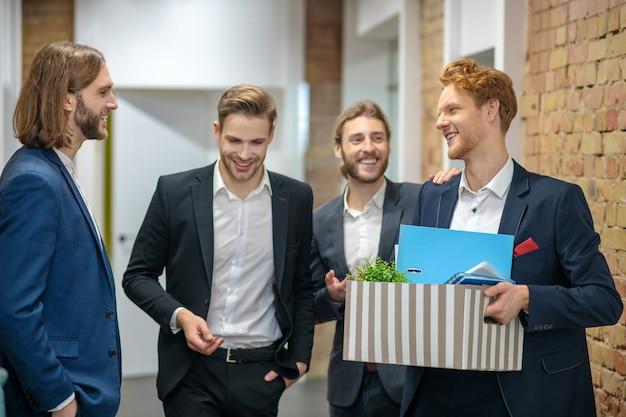 Czterech młodych dorosłych wesołych mężczyzn w garniturach stojących, komunikujących się na korytarzu biura