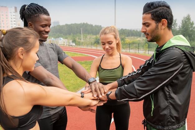 Czterech młodych ludzi międzykulturowych w odzieży sportowej robiąc stos rąk stojąc na stadionie