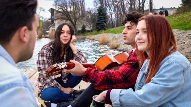 Czterech młodych przyjaciół śpiewających, odpoczywających i grających na gitarze w pobliżu jeziora w parku