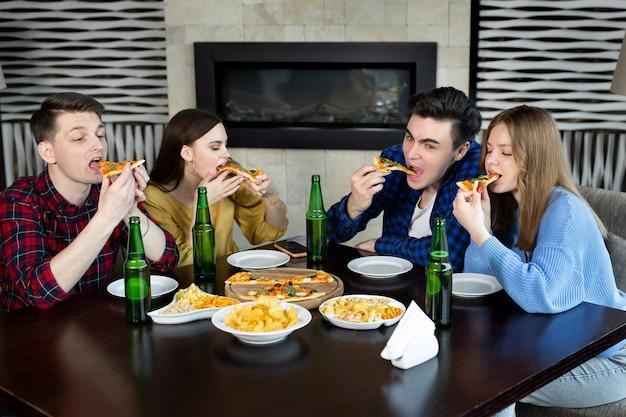 Czterech młodych wesołych ludzi jedzących pizzę i pijących piwo