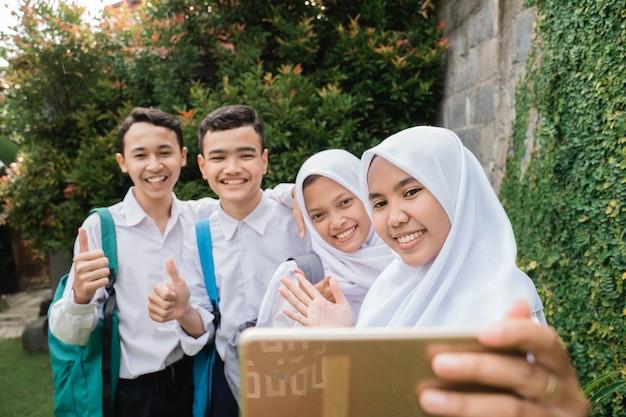 Czterech nastolatków w gimnazjalnych mundurkach robi razem selfie za pomocą smartfona