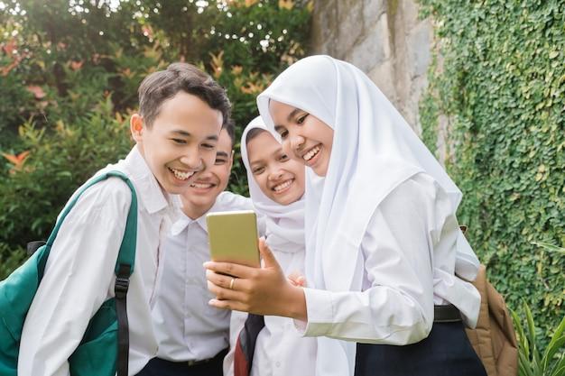 Czterech nastolatków w gimnazjalnych mundurkach używających i patrzących na telefony komórkowe