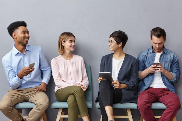 Czterech nieznajomych młodych ludzi prowadzi ożywioną rozmowę