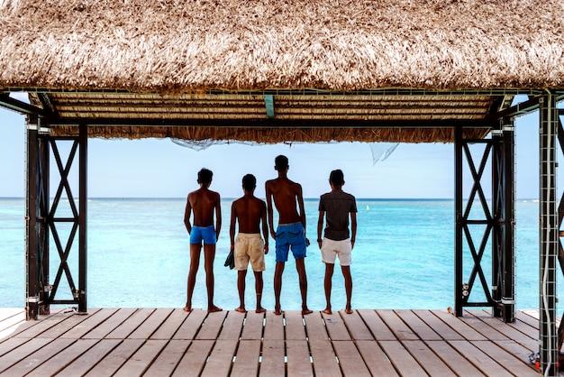 Czterech opalonych chłopców w strojach kąpielowych stojących na doku i patrząc na piękny niebieski ocean. odwrócili się plecami.