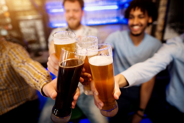 Czterech przyjaciół brzękających ze szklankami piwa w pubie.