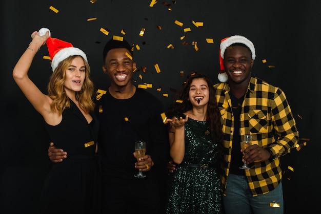 Czterech przyjaciół różnych narodowości rzuca konfetti w czapki i poroże mikołaja i pije szampana na czarnym tle. towarzystwo młodych ludzi świętuje boże narodzenie i nowy rok.