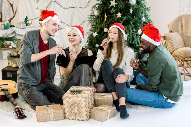 Czterech przyjaciół w czapkach mikołaja śmiejących się na przyjęciu bożonarodzeniowym z szampanem w przytulnie urządzonym pokoju