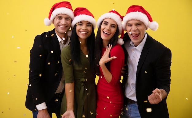 Czterech przyjaciół w świątecznych czapkach bawi się w sylwestra, śmiejąc się, uśmiechając i rzucając w powietrze jaskrawe, złote konfetti.
