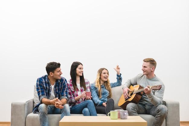 Czterech przyjaciół z gitarą siedzi na kanapie na białym tle ściany
