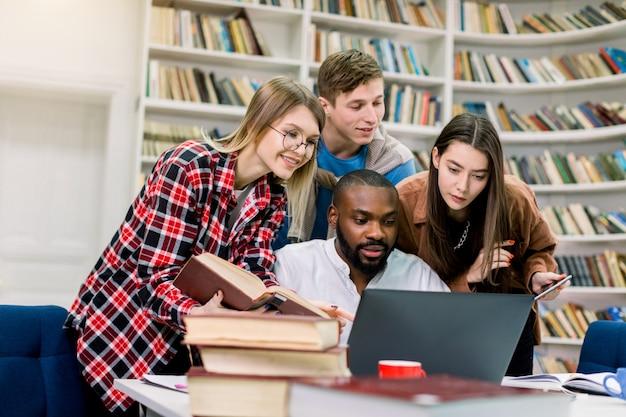 Czterech radosnych wielorasowych studentów w bibliotece, którzy razem studiują i przygotowują się do egzaminów, używając laptopa do wyszukiwania informacji w internecie